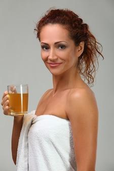 Mooie vrouw in handdoek met kruidenthee