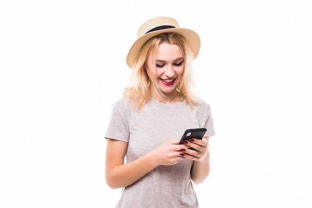 Mooie vrouw in heldere hoed die een nieuwe mobiele telefoon met behulp van