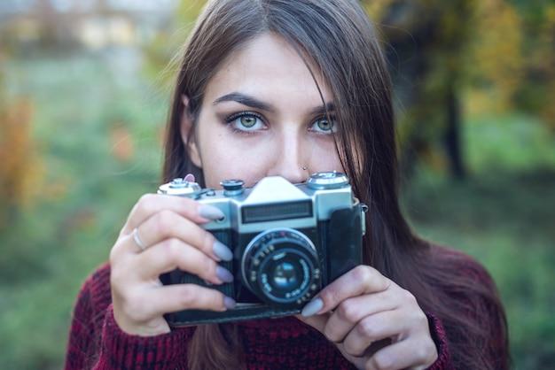 Mooie vrouw in herfst park houdt vintage retro camera