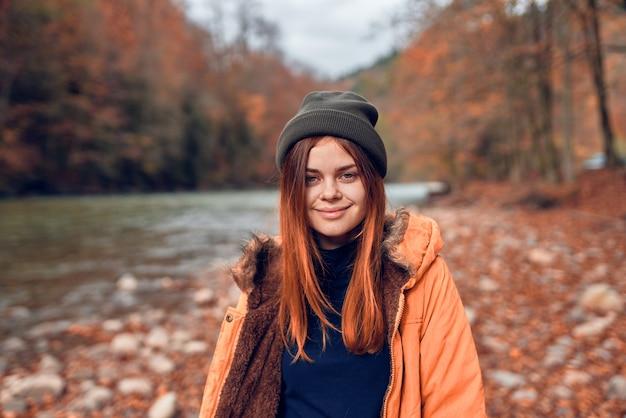 Mooie vrouw in herfstkleren in de gevallen bladeren van de bosrivier river