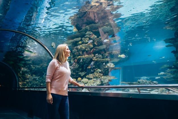 Mooie vrouw in het aquarium die naar de vissen kijkt