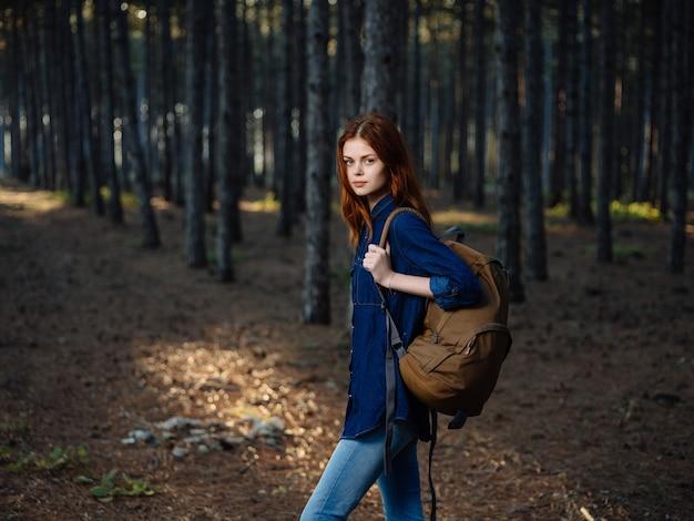 Mooie vrouw in het bos met een natuurwandeling met rugzak