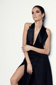 Mooie vrouw in het modellicht van de zwarte kledingsglamour.