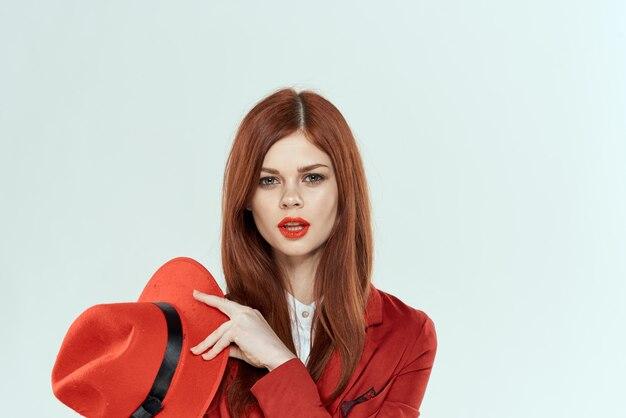 Mooie vrouw in het rode licht van de de make-up elegante stijl van de hoedenblazer