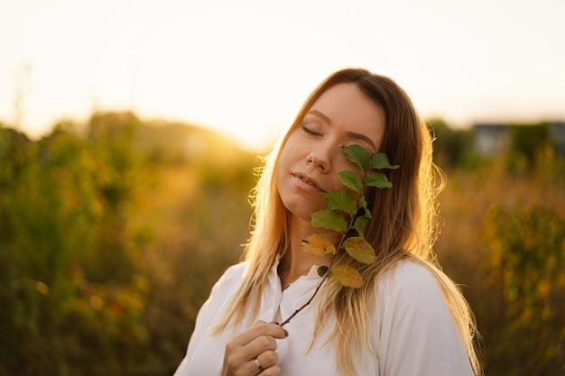 Mooie vrouw in het veld meisje houdt een takje met bladeren in de buurt van haar gezicht dat één oog bedekt