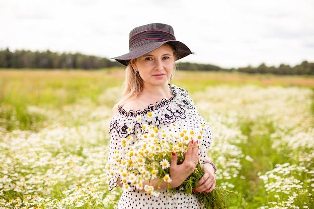 Mooie vrouw in het veld met bloemen. hoge kwaliteit foto