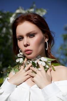 Mooie vrouw in het voorjaar in de takken van bloeiende appelstruiken