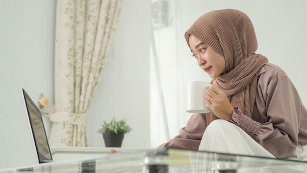 Mooie vrouw in hijab die vanuit huis werkt met laptop onder het genot van een drankje