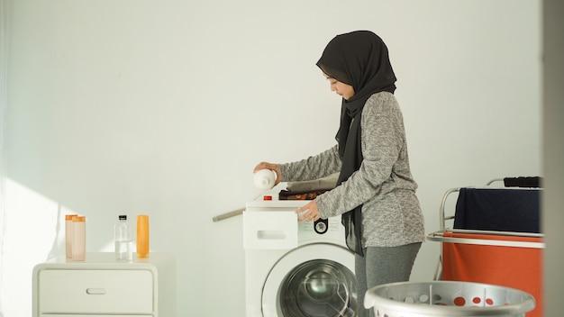 Mooie vrouw in hijab giet wasmiddel voor haar was thuis