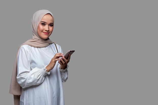 Mooie vrouw in hijab houdt een mobiele telefoon glimlachend en kijkt naar de camera geïsoleerd op een effen achtergrond