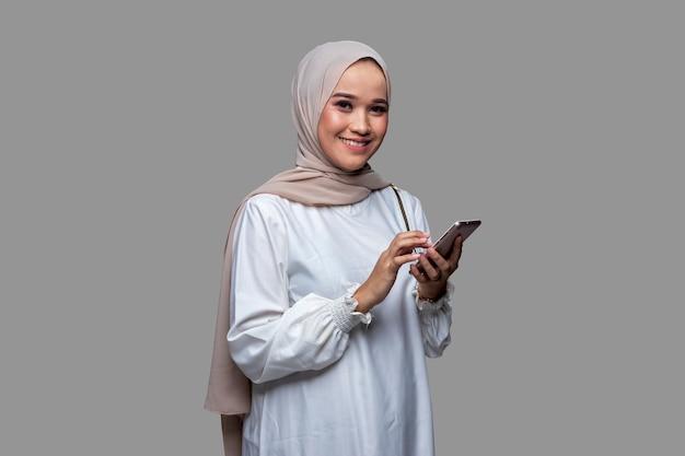 Mooie vrouw in hijab houdt een mobiele telefoon glimlachend en kijkt naar de voorkant