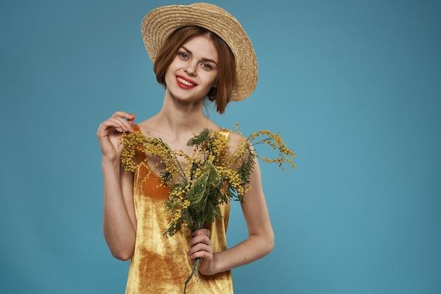 Mooie vrouw in hoed boeket bloemen vakantie blauwe achtergrond
