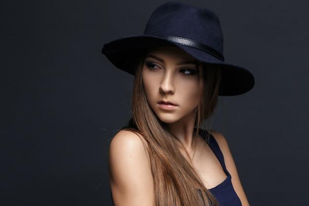 Mooie vrouw in hoed. donker