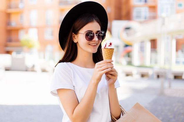 Mooie vrouw in hoed en zonnebril met boodschappentassen en ijs praten op straat in de stad
