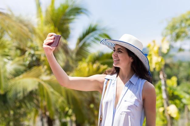 Mooie vrouw in hoed maken selfie foto portret over tropische boslandschap happy smiling cut