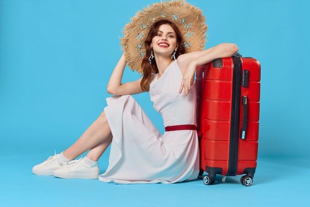 Mooie vrouw in hoed met rode koffer zittend op de vloer blauwe reisachtergrond