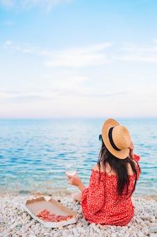Mooie vrouw in hoed op het strand op picknick met pizza en wijn