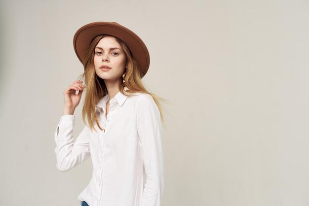 Mooie vrouw in hoed wit overhemd elegante stijl mode lichte achtergrond