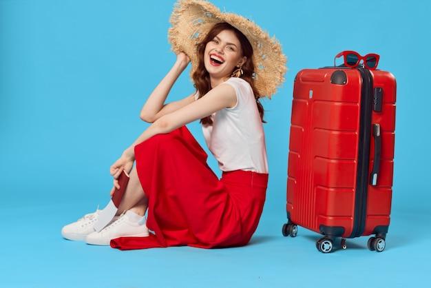 Mooie vrouw in hoed zittend op de vloer met rode koffer reisbestemming