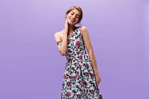 Mooie vrouw in hoge geesten vormt op paarse achtergrond. mooie jonge dame met rode lippen in bloemenkleren die op geïsoleerde achtergrond glimlachen.
