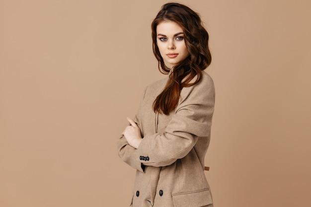 Mooie vrouw in jas op beige achtergrond en bijgesneden weergave kopie ruimte