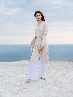 Mooie vrouw in jas poseren strand frisse lucht elegante stijl. hoge kwaliteit foto