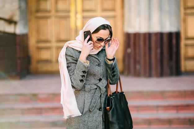 Mooie vrouw in jas spreekt via de telefoon op straat