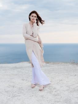 Mooie vrouw in jas zand zomer elegante stijl