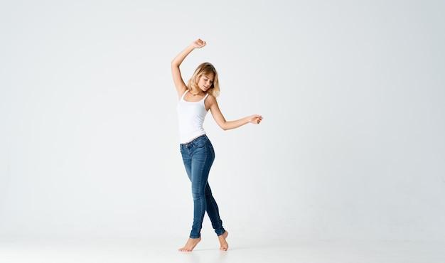 Mooie vrouw in jeans bewegingen dansen op blote voeten lichte achtergrond