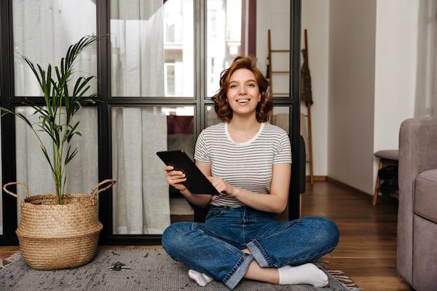 Mooie vrouw in jeans broek zit op de vloer, houdt tablet en kijkt naar de camera.