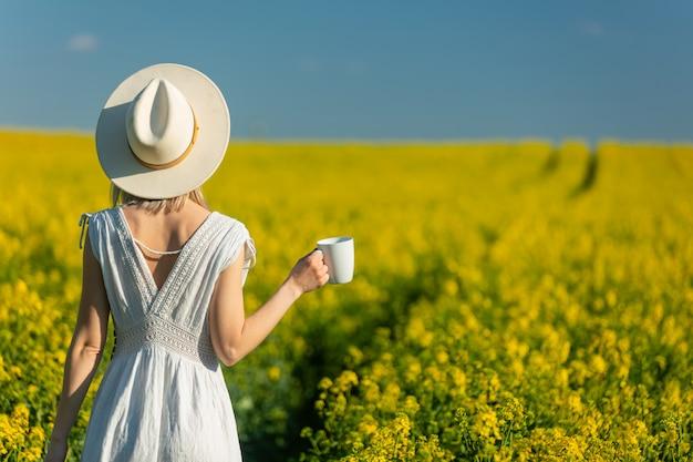 Mooie vrouw in jurk met kop koffie in koolzaad veld