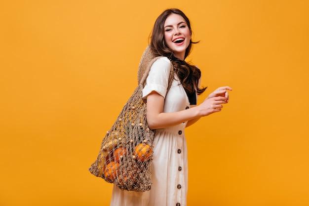 Mooie vrouw in katoenen jurk lacht en houdt string tas met fruit. portret van dame met golvend haar op oranje achtergrond.