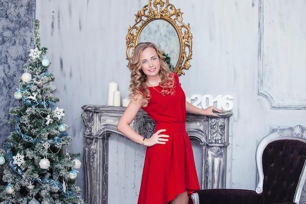 Mooie vrouw in kerst interieur viert gelukkig op het oppervlak van de kerstboom in het nieuwe jaar
