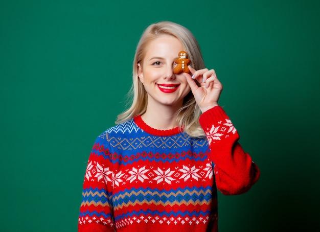 Mooie vrouw in kerstmissweater met koekjes van de peperkoekman
