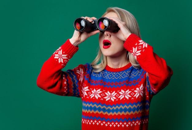 Mooie vrouw in kerstmissweater met verrekijker