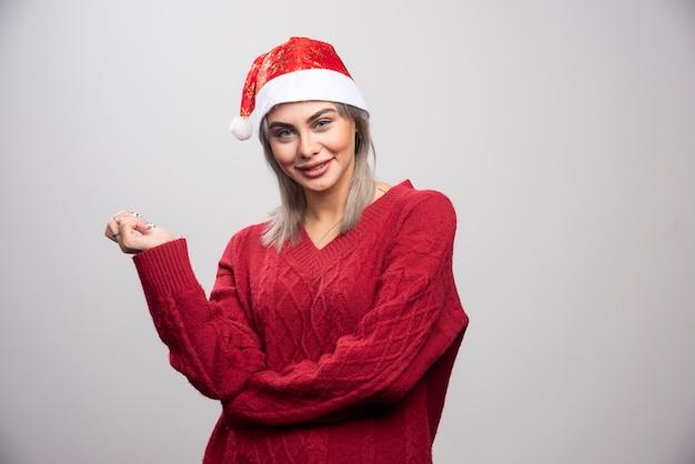 Mooie vrouw in kerstmuts die gelukkig op grijze achtergrond kijkt.