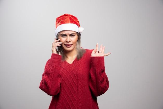 Mooie vrouw in kerstmuts intens praten op mobiel.