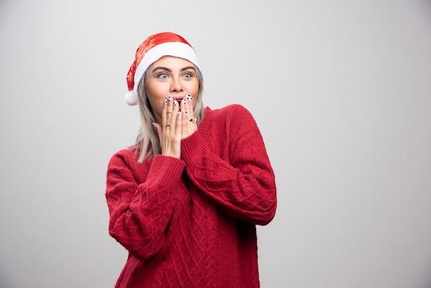 Mooie vrouw in kerstmuts wordt verrast.