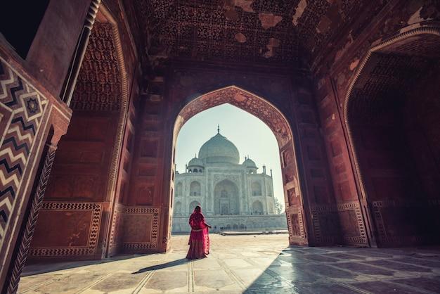 Mooie vrouw in klederdrachtkostuum, aziatische vrouw die typische saree / sari-kleding identiteitscultuur van india draagt. taj mahal scenic de ochtendweergave van het taj mahal-monument in agra, india.