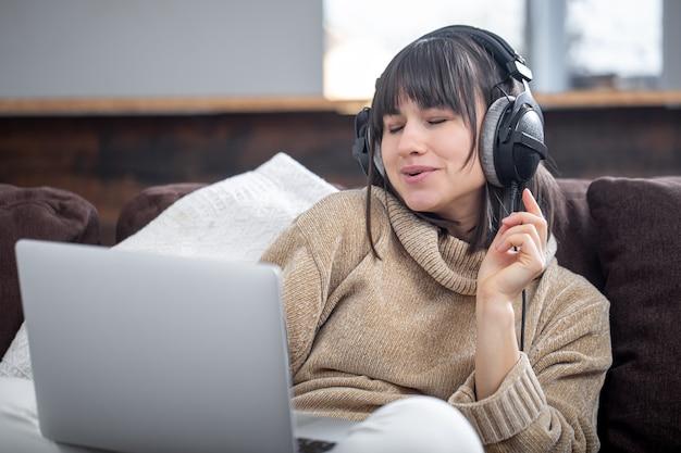 Mooie vrouw in koptelefoon luisteren naar muziek thuis op de bank met een laptop.