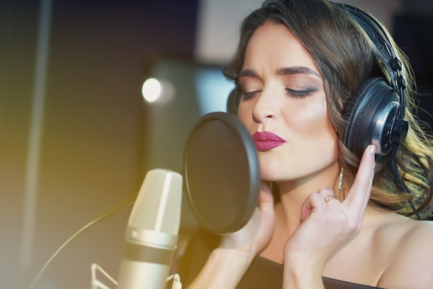 Mooie vrouw in koptelefoon neemt een lied op in een professionele opnamestudio