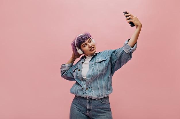 Mooie vrouw in koptelefoon neemt selfie op roze. krullende vrouw in spijkerjasje maakt foto.