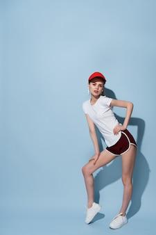 Mooie vrouw in korte broek poseren mode glamour blauwe achtergrond