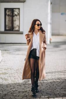 Mooie vrouw in laag het drinken koffie buiten in de straat