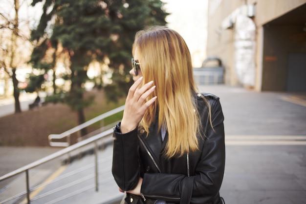 Mooie vrouw in leren jas buitenshuis poseren mode wandeling. hoge kwaliteit foto