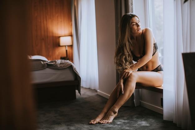 Mooie vrouw in lingerie die en buiten het venster in haar mooie flat zitten kijken