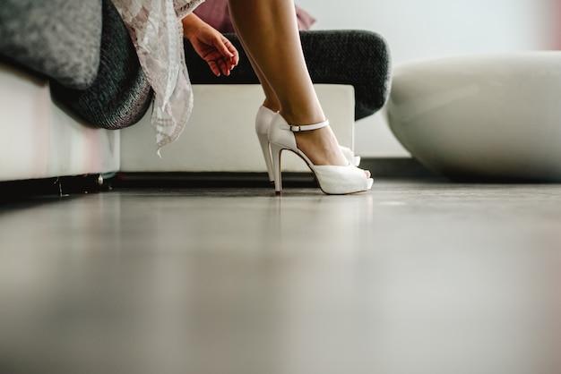 Mooie vrouw in lingerie die op sommige hoge hielen op haar aardige lange benen zet.
