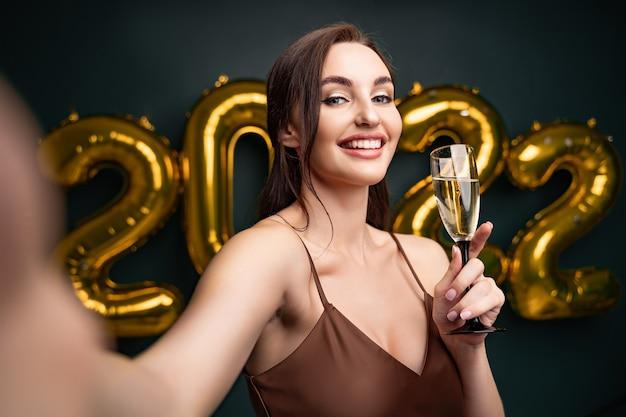Mooie vrouw in luxe moderne jurk doet selfie met champagne voor gouden ballonnen isol...