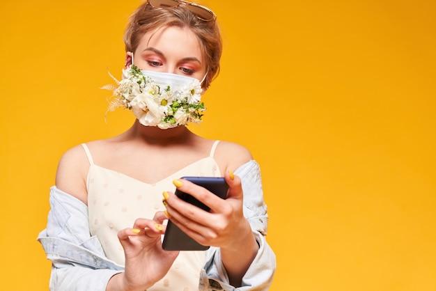 Mooie vrouw in medisch masker met bloemontwerp, die telefoon houden