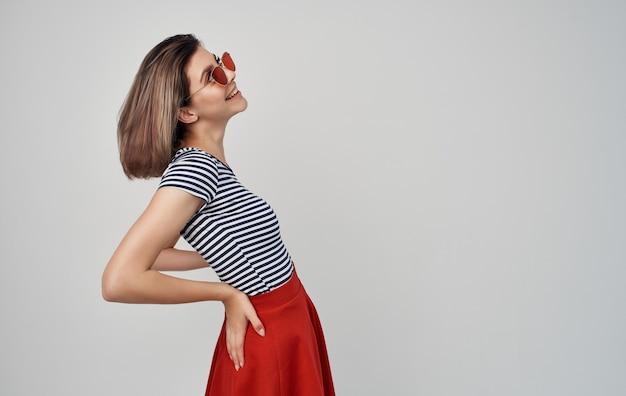 Mooie vrouw in mode kleding rode rok gestreepte t-shirt zonnebril gebaren met handen.